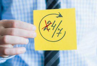 Ein Man im blauen Hemd mit einem Post-It in der Hand auf dem 24/7 steht und die 2 aus der 24 durchgestrichen ist