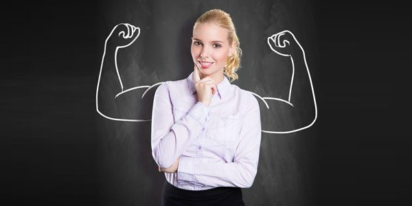 Frau vor Tafel, auf der angespannte Arme mit großen Muskeln zu sehen sind