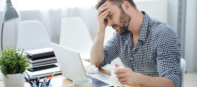 Verschnupfter junger Mann in hellem Büro mit einem Taschentuch in der Hand vor einem Laptop. Die andere Hand hält er sich an die Stirn. Er verzieht ein bisschen sein Gesicht, da er anscheinend Kopfschmerzen oder Fibre hat. Das Büro ist hell und modern eingerichtet.