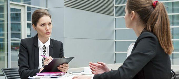 Fangfragen im Bewerbungsgespräch / auf dem Foto: Eine streng gekleidete Personalerin fragt eine Bewerberin in einem Vorstellungsgespräch aus und hackt dabei eine Liste ab.