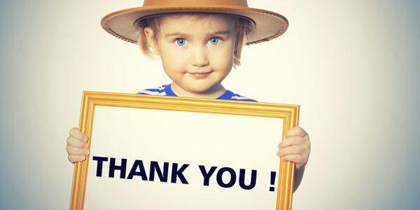 """Kleiner Junge mit einem eingerahmten Schild auf dem """"Thank You!"""" steht."""