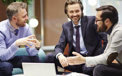 Drei entspannte, junge Geschäftsleute vor einem Laptop in Sessel und Sofa sitzend miteinander redend.