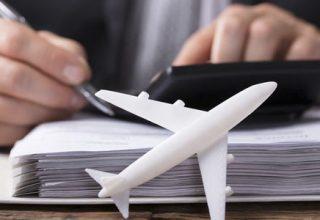 Businessmann mit Kugelschreiber vor einer Akte und einem kleinen weißen Modellflugzeug seine Reisekostenabrechnung machend