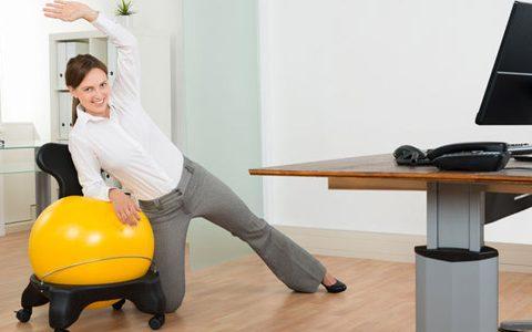 Frau macht aktive Pause im Büro. Streckt Gliedmaßen vor Schreibtisch mit Hilfe eines gelben Gymnastikballs.
