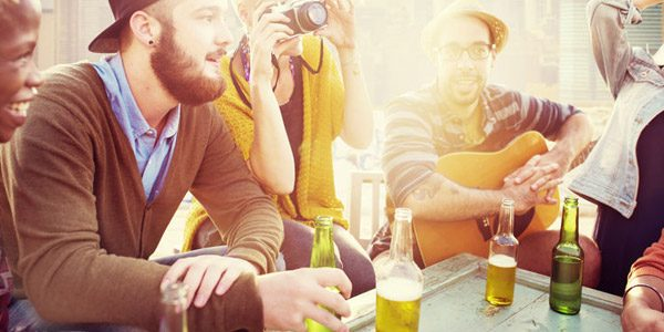 Junge Leute sitzen mit Getränken in der Sonne draußen am Tisch vor der Arbeit zusammen.
