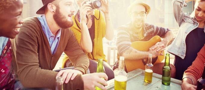 Junge Leute sitzen mit Getränken in der Sonne draußen am Tisch zusammen.