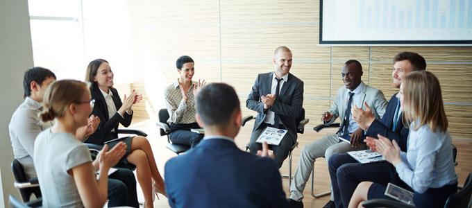 Büromenschen sitzen in Besprechungsraum zusammen und klatschen.