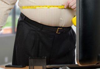 Ein übergewichtiger Mann steht am Arbeitsplatz und misst seinen Bauch mit einem Maßband.