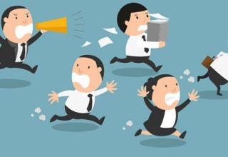 Karikatur mit fünf Personen auf blauem Hintergrund. Vier Personen laufen vor einer Person weg. Die weglaufenden Personen stellen Kollegen dar, die fast panisch von der fünften Person flüchten, welche mit einem Megaphone in der Hand hinterherläuft.