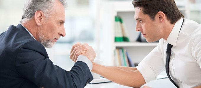 Zwei Männer im Business-Look beim Armdrücken. Beide schauen sich dabei entschlossen in die Augen. Fokus liegt auf den Männern, im Hintergrund ist leicht geblurrt ein Büro zu erkennen.