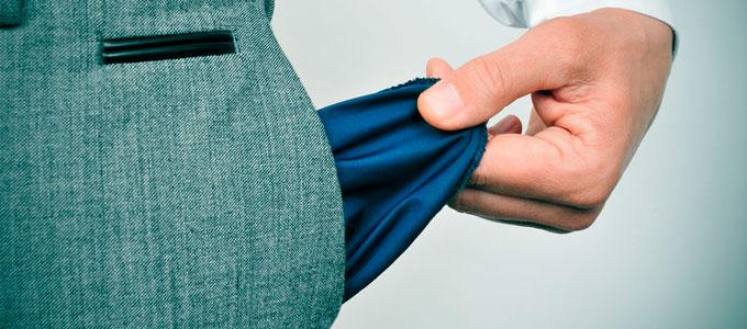 Eine Person zieht mit seiner Hand die innen Tasche seiner Hose heraus. Das Bild soll verdeutlichen, dass sich in der Hosentasche nichts befindet.