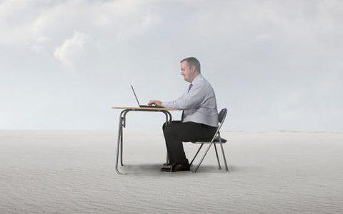 Ein Mann sitzt am Schreibtisch, mitten in der Wüste, und arbeitet an seinem Laptop. Weit und breit ist nichts um ihn herum zu sehen, außer Sand.