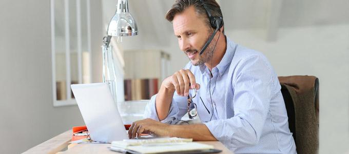 Ein Mann sitzt offensichtlich zu Hause am Schreibtisch vor seinem Laptop, mit Headset auf dem Kopf und geht seiner Arbeit nach.