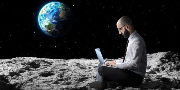 Ein Mann sitzt im Schneidersitz mit seinem Laptop auf den Beinen im Weltall, höchstwahrscheinlich auf dem Mond. Im Hintergrund ist das schwarze Weltall mit vereinzelten Sternen und die von der Sonne angestrahlte Erde zu sehen.