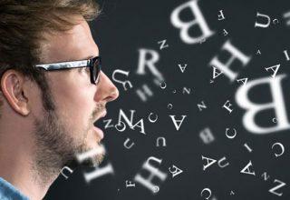 Es wird ein junger Mann, sprechend oder singend, im Seitenprofil abgebildet. Vor ihm wirbeln diverse Buchstaben in der Luft herum.