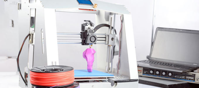 Ein 3D Drucker erzeugt ein Objekt. Das Objekt ist rosa, anhand der Form lässt sich jedoch noch kein Gegenstand erkennen. Im Hintergrund ist lediglich eine weiße Wand, als auch ein aufgeklapptes Notebook zu erkennen.