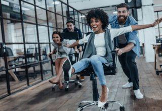 """Humor im Job / auf dem Foto: Mitarbeiter haben Spaß im Büro und machen eine """"Bürostuhl Polonäse""""."""
