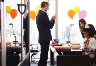 Ein Büro, geschmückt mit bunten Luftballons und Happy Birthday Banner. Inmitten der Räumlichkeiten sind vier Personen am Schreibtisch versammelt. Eine junge Frau mit Partyhut auf dem Kopf sitzt auf dem Bürostuhl und strahlt vor Freude. Vor ihr auf dem Tisch eine Geburstagstorte. Um sie herum stehen zwei Kollegen und eine Kollegin. Einer der Kollegen fotografiert das Szenario mit seinem Smartphone.