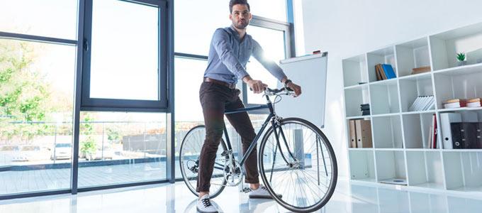 Ein junger Mann auf einem Fahrrad inmitten eines Büroraums / Meetingraums. Der Raum ist auf Grund einer vollverglasten Fensterfront hinterm jungen Mann durch das Tageslicht hell erleuchtet. Der Raum ist ausgestattet mit Regal mit Ordnern und Akten, als auch ein unbeschriebenes Flipchart.