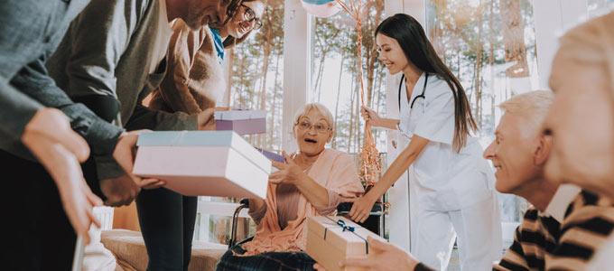 Gemütliches Zusammensitzen mit mehreren Personen im Altersheim. In fröhlicher Atmosphäre werden den Heimbewohnern von Besuchern Geschenke überreicht.
