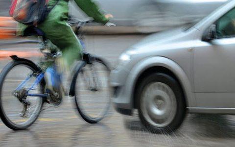 Eine Unfallsituation mit Fahrrad und Auto auf einer Straße. Das Auto droht mit dem Fahrrad zu kollidieren. Das Foto ist stark geblurrt, um die Geschwindigkeit beider Verkehrsteilnehmer zu simulieren.