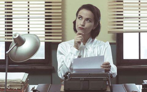 Zeitreise ... das Büro im Jahr 1969 / auf dem Foto: Eine Sekretärin, die an einer Schreibmaschine arbeitet und nachdenkt.