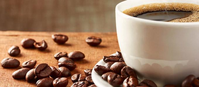 Der kleine Kaffee-Ratgeber / auf dem Foto: Eine heiße Tasse Kaffee, umrahmt von Kaffeebohnen.