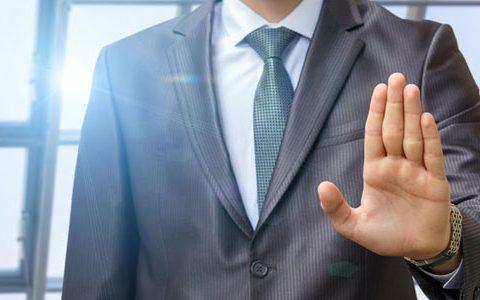Keine Chance auf die Stelle... Dem Mitarbeiter eine Absage erteilen / auf dem Foto: Ein Mann steht uns gegenüber mit erhobener Hand, wobei die Handfläche zu sehen ist. Die verneinende Geste symbolisiert Ablehnung.