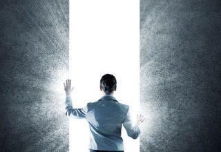 Jobwechsel... So klappt der Neustart / auf dem Foto: Ein Mann steht in einem Spalt zwischen zwei Wänden. Aus dem Spalt erleuchtet ein helles Licht. Was verbirgt sich wohl dahinter? Wir können es nicht sehen, lediglich ein tiefes Weiß strahlt uns entgegen.