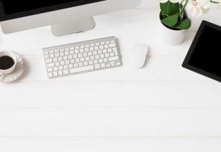 Minimalismus am Arbeitsplatz / auf dem Foto: Ein sehr aufgeräumter Büro-Arbeitsplatz mit Desktop-PC und den wichtigsten Arbeitsutensilien (Tablet, Bildschirm, Tastatur, Maus, Notizblock, Stift, Brille, Smartphone, Pflanze und eine Tasse Kaffee)