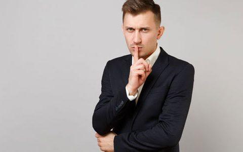 Ghosting im Bewerbungsverfahren Wenn der Arbeitgeber plötzlich schweigt / Auf dem Foto: Ein Mann symbolisiert mit seinem Zeigefinger vor seinem geschlossenen Mund Stille bzw. Schweigen und schaut entnervt.