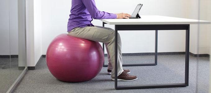 Sitzball als Alternative zum Bürostuhl? / auf dem Foto: Ein Mann sitzt auf einem Sitzball an einem Tisch und arbeitet am Tablet-PC.