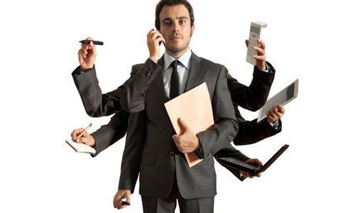 Zu-viele-Talente-Effekt. Das bedeutet er für Unternehmen / auf dem Foto: Multitasking im Beruf. Ein Mann mit acht Armen, jeder Arm beschäftigt sich mit einem anderen Aufgabenfeld. Vom Taschenrechner bis zum Notizblock ist alles abgedeckt. Telefonieren, während gleichzeitig eine E-Mail im Notebook verfasst wird, der Mann hat alles im Griff.