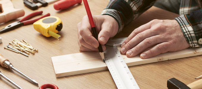 Handwerk als Hobby / auf dem Foto: Ein Mann bereitet ein DIY-Projekt vor und misst ein Holzstück aus. Handwerker malt mit Hilfe eines Lineals mit einem Bleistift eine Linie auf ein Holzbrett. Um ihn herum liegen weitere Handwerksutensilien wie Nägel, Maßband, Zange, Hammer und Schraubendreher. Fokus des Bildes sind die Hände des Handwerkers.