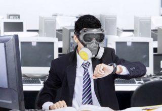 Luftqualität im Büro / auf dem Foto: Ein Angestellter sitzt mit Gasmaske in einem Büroraum voller Computer und schaut auf die Uhr. Geschäftsmann, in Anzug und Krawatte, sitzt am Arbeitsplatz im Großraumbüro, umgeben von zahleichen Computern und Bildschirmen, mit Gasmaske und Augenschutzbrille und schaut auf seine Armbanduhr.