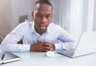 Digitale Spracherkennung / auf dem Foto: Geschäftsmann diktiert der Software einen Text. Ein Mann sitzt an einem Schreibtisch, sein Büro ist sehr schlicht und in weiß gehalten. Er selber trägt ein weißes Hemd. Er spricht offensichtlich mit einem Sprachassistenten, den er dabei mit den Augen fixiert.