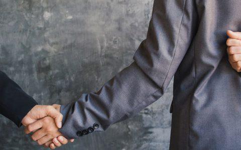 Toxische Kollegen: Giftspritzen im Job ausbremsen / auf dem Foto: Zwei Kollegen geben sich die Hand. Eine der Personen hält dabei hinterm Rücken ein Messer in der anderen Hand.
