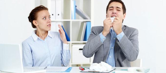 Husten, Schnupfen, Heiserkeit: Willkommen in der Erkältungszeit / Auf dem Foto: Kollegin und Kollege sitzen nebeneinander am mit Taschentüchern übersätem Schreibtisch im Büro. Der Kollege niest in ein Taschentuch, welches er mit beiden Händen vor sein Gesicht hält. Seine Sitznachbarin hält zum Schutz ihre Hand hoch und schaut ihn besorgt, zugleich jedoch angewidert an.