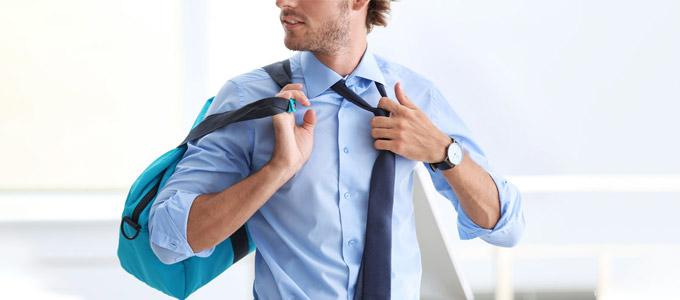New Work: Arbeiten, wie es gefällt // auf dem Foto: Ein Mann, leger gekleidet, lockert seine Kravatte und trägt dabei seine Sporttasche lässig über der Schulter.