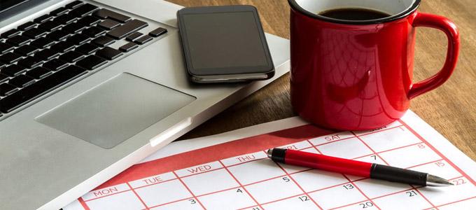 Welcher Kalender-Typ sind Sie? / auf dem Foto: Monatskalender aus Papier liegt neben Smartphone und Notebook auf dem Schreibtisch. Schreibtisch mit folgenden Utensilien: Laptop, Smartphone, rote Kaffeetasse mit schwarzem Kaffee gefüllt, Terminplaner und Kugelschreiber.