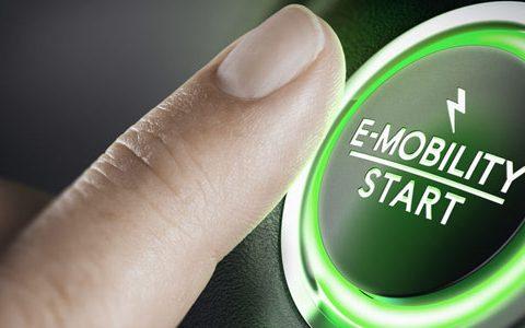 """MOIA - Mobilität der Zukunft? / auf dem Foto: Finger drückt auf grüne Taste mit der Aufschrift """"E-Mobilität starten""""."""