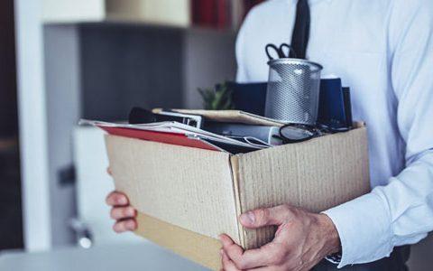 Kündigungsschutzklage / auf dem Foto: Da ihm gekündigt wurde, hat ein Büroangestellter seinen Schreibtisch geräumt und seine Utensilien im Karton gepackt.
