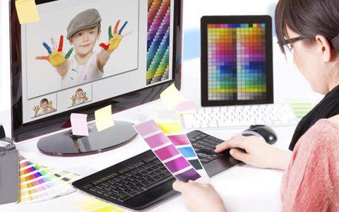 Künstlersozialkasse / auf dem Foto: Eine Grafik-Designerin sitzt vor dem Computer und probiert verschiedene Farbkompositionen aus.