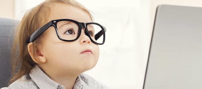 Weiterbildung mit Online-Kursen / auf dem Foto: Ein kleines Kind mit großer Brille sitzt am Computer.