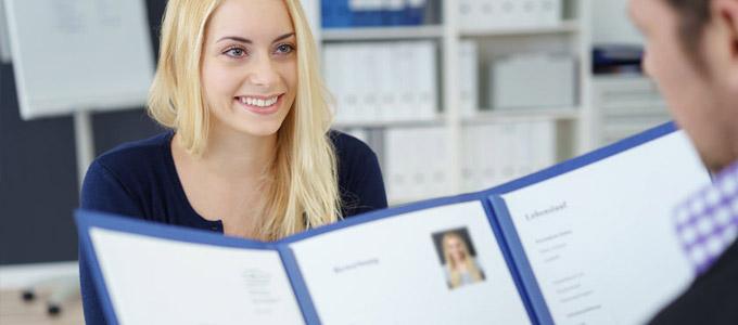 Schriftarten für die Bewerbung / auf dem Foto: Eine Frau sitzt dem Personalleiter gegenüber, der sich ihre Bewerbungsunterlagen anschaut.