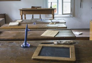 Klassentreffen / auf dem Foto: Ein altes Klassenzimmer mit Tischen, Lehrer-Pult und diversen Schulutensilien.