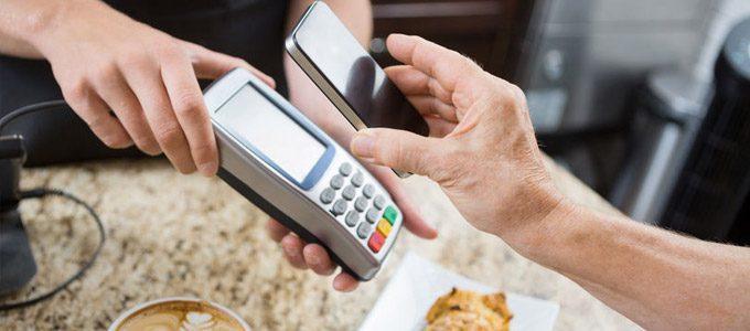 Zahlungsarten online und offline  / auf dem Foto: Ein Kunde bezahlt seinen Kaffee und Kuchen mit dem Smartphone / Handy.