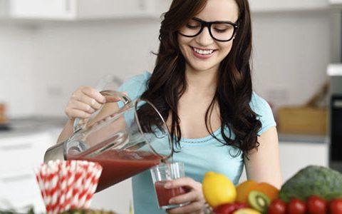 Smoothies & Co. - Gesunde Ernährung im Büro / auf dem Foto: Eine junge Frau hat sich einen Gemüse-Smoothie im Mixer zubereitet und schüttet sich das Getränk in ein Glas.