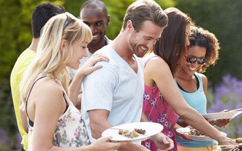 Grillabend mit den Kollegen / auf dem Foto: Der Gastgeber steht am Grill und verteilt das Essen an seine Arbeitskollegen.