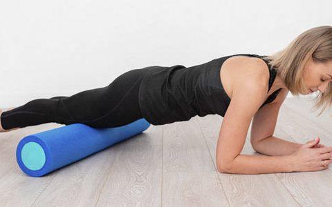 Verspannungen mit der Faszienrolle bekämpfen / auf dem Foto: Eine Frau verwendet eine Faszienrolle, um sich aufzuwärmen.